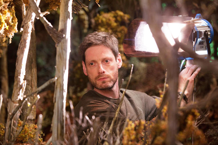 <p>Director of Photography Tristan Oliver adjusts the on-set lighting.</p>