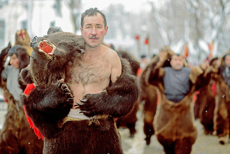 <p>A Romanian man wears the skin of a bear in a Romanian festival of some complexity.</p>