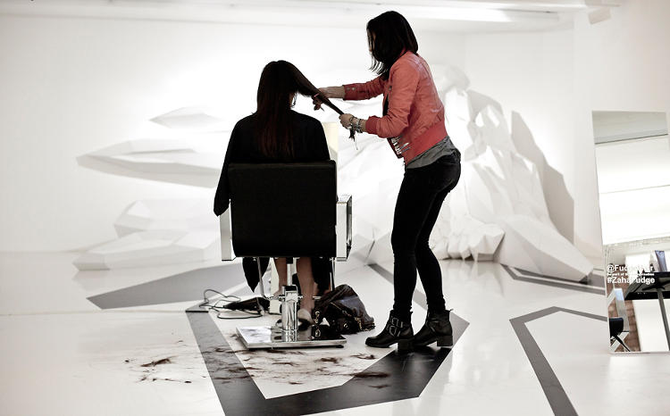 <p>The work stations were arrayed across the white-walled space, along a jagged black supergraphic pattern applied to the floor.</p>