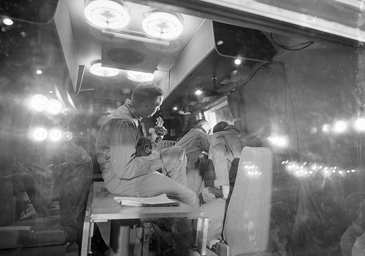 <p><strong> Quarantine Ukelele</strong><br /> Interior view of a Mobile Quarantine Facility (MQF), showing the Apollo 11 crewmen soon after they arrived at Ellington Air Force Base after a flight from Hawaii aboard a U.S. Air Force C141 jet transport. Neil Armstrong is strumming on a ukelele. Michael Collins (right foreground) and Edwin E. Aldrin Jr. (right background) are looking out the window. The other people in the picture are MQF support personnel. This picture was taken during brief welcome home ceremonies.</p>