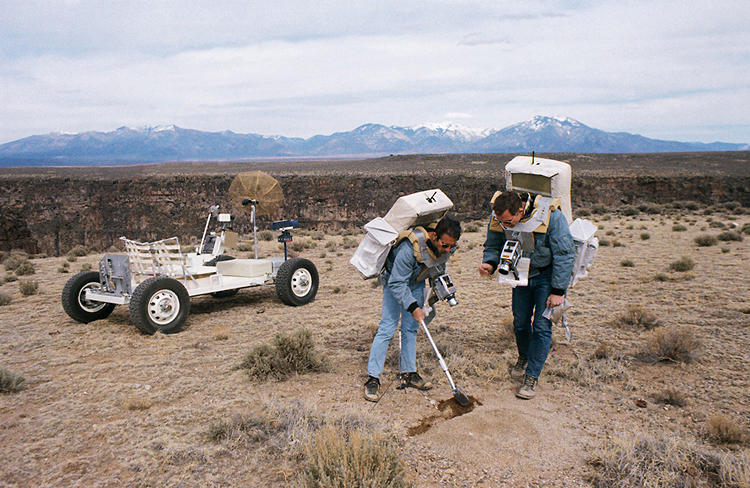 <p><strong>Lunar Rover, Driving School</strong><br /> Two members of the prime crew of the Apollo 15 lunar landing mission collect soil samples during a simulation of lunar surface extravehicular activity in the Taos, New Mexico, area. Astronaut James B. Irwin, lunar module pilot, is using a scoop. Astronaut David R. Scott (right), commander, is holding a sample bag. On the left is a Lunar Roving Vehicle trainer.</p>