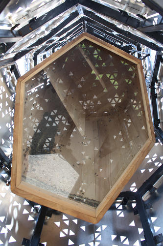 <p>Inside, the &quot;bee cab,&quot; a wooden box containing the hive, is fitted with a laminated glass bottom that lets visitors (and beekeepers) peer inside. The hive is mounted on tracks and can be lowered up and down the inside of the tower.</p>