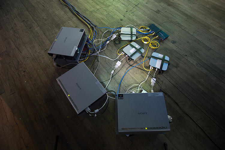<p>The computers play the files back on a big screen as they download, resulting in a frenetic audiovisual mash-up that plays out across several big screens.</p>