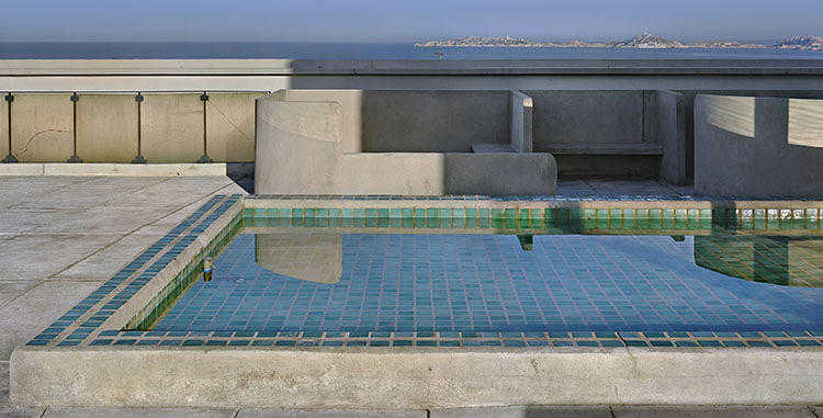 <p>The rooftop of the Unité d'Habitation in Marseilles features a wading pool and amorphic concrete &quot;boulders&quot; that allude to the sea and mountains beyond.</p>  <p>Photograph: Richard Pare</p>