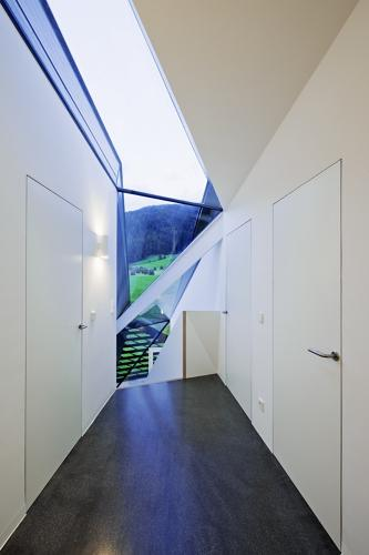 <p>Mountain sunlight and views spill in from a narrow, wedge-like skylight and bounce off the predominately white interiors.</p>