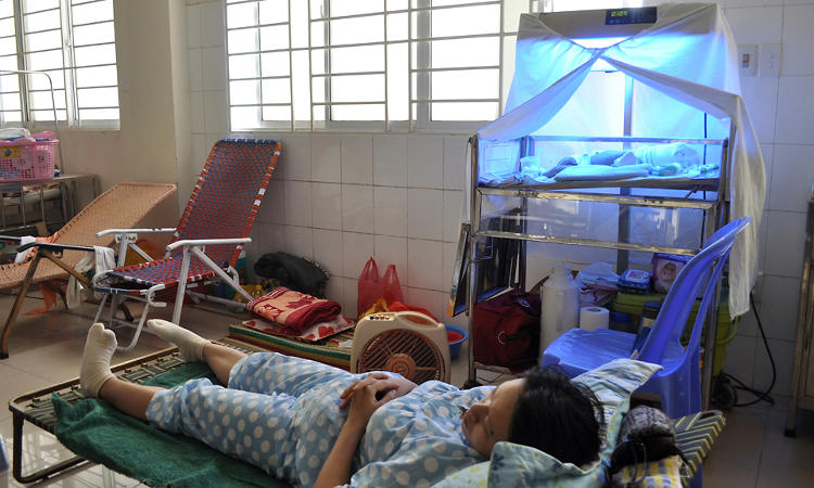 <p>A mother on a makeshift bed as her child receives phototherapy nearby at Da Nang Hospital for Women &amp; Children in Vietnam.</p>