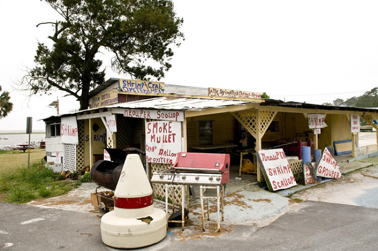 Fred's Retail sells the daily catch -- Gulf shrimp, fresh oysters, and his specialty, smoked mullet. His business was heavily trafficked as tourists moving into beachfront rental homes stopped by to stock up on his seafood for the holiday weekend.