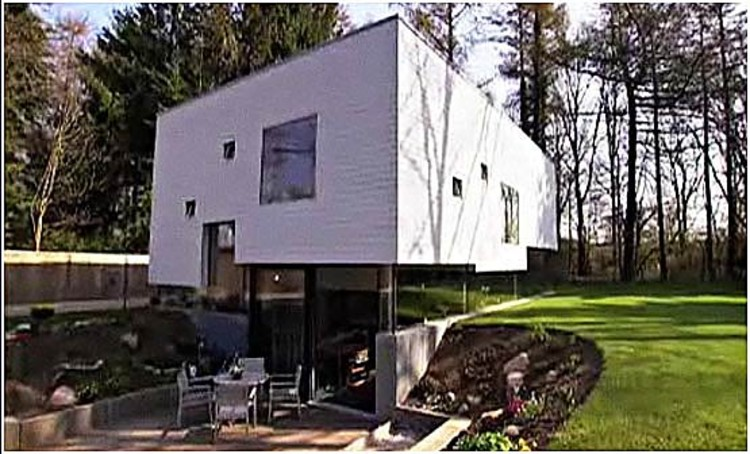 Inside this ultra modern stork-like box home, features include, an open concept design for communal living, lots of windows, a remarkable two-story bookcase and a tiny carbon footprint.