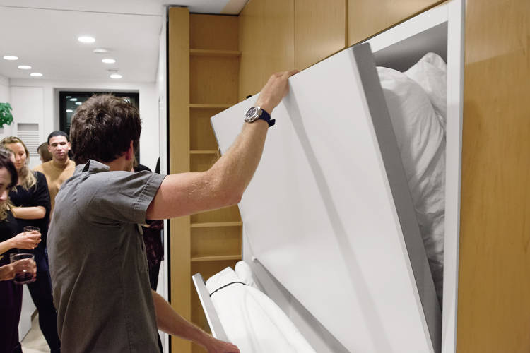 <p>Graham demonstrates the pull-out guest beds in his apartment.</p>