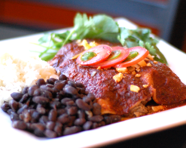 <p>Carnitas enchiladas: Braised pork with red onion and white cheddar wrapped in white corn tortillas baked in red chile sauce, served with black beans and Spanish rice.</p>