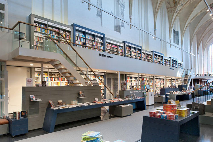 <p>Opposite the large retail floors is a two-story gallery lined with bookshelves. This creates a border that helps delineate the shop from the worship space.</p>