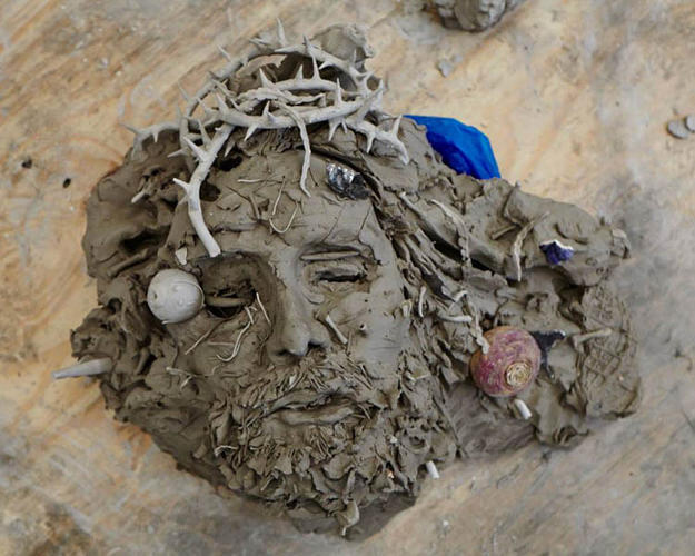 <p>A head of Jesus in a crown of thorns seems to melt into the ground.</p>  <p>Adrián Villar Rojas, Studio, London, 2013. Image courtesy Serpentine Gallery © Jamie Smith</p>