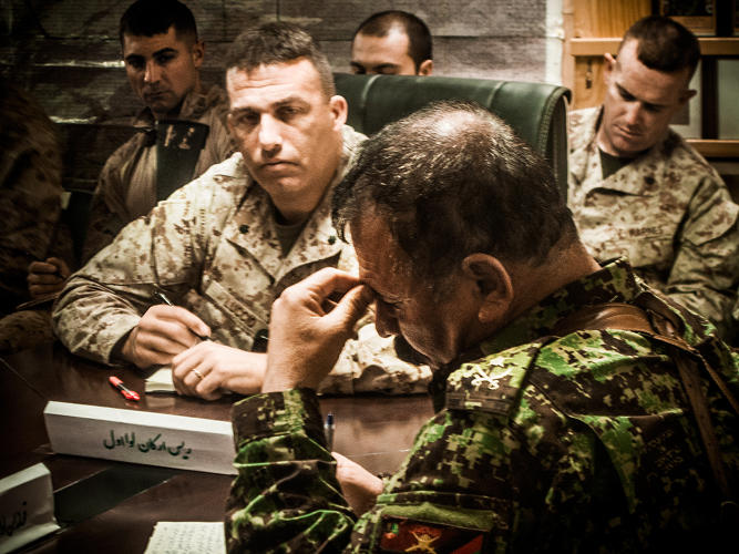 <p>Lt. Col. Douglas Luccio (left) and Lt. Col. Phil Treglia (right) sit in on the 1/215 brigade's morning meeting, with Col. Muhammed Salwar (center), the brigade executive officer.</p>