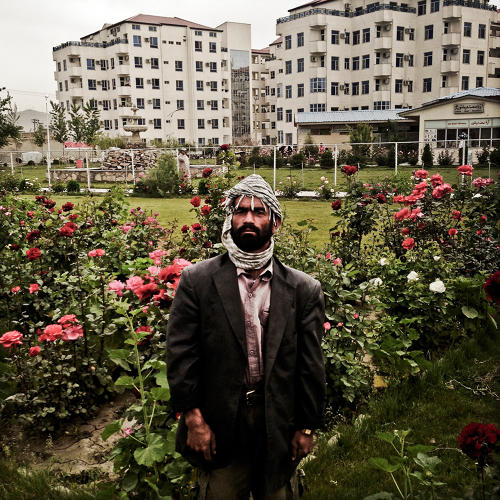 <p>A gardener stands in front of one of the buildings in a housing complex called New Aria City in Kabul.</p>