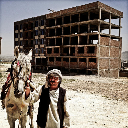 <p>In front of a construction site in Kabul, a horseman from Mazar-e-Sharif sells rides on a horse for entertainment.</p>