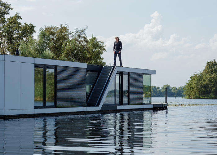 <p>Architect Koen Oithuis astride a floating villa he designed in the village of Kortenhoef.</p>