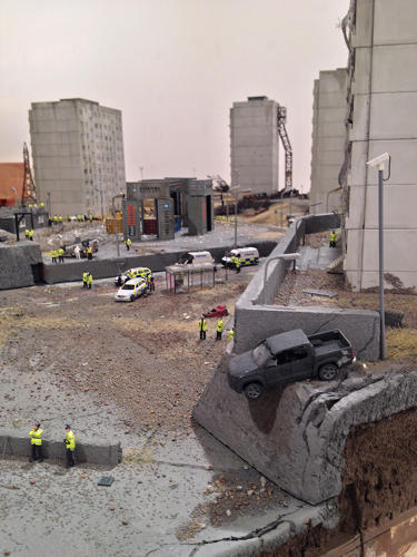 <p>The ground looks charred. A delivery truck has crashed through a McDonald's, leaving one of the arches broken on the ground. Lights flash on miniature ambulances.</p>