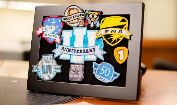 <p>Every employee has a velcro patch at their desk that can hold badges earned for meeting goals, kind of like scout patches.</p>