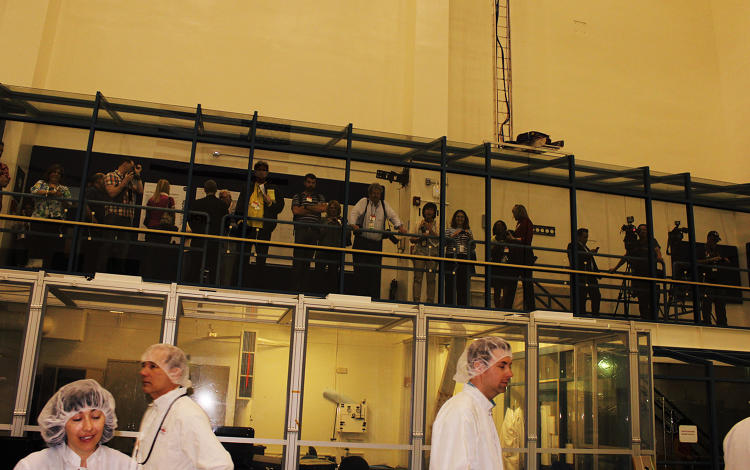 <p>A second shift of reporters awaits its turn in the clean room from the observation deck.</p>
