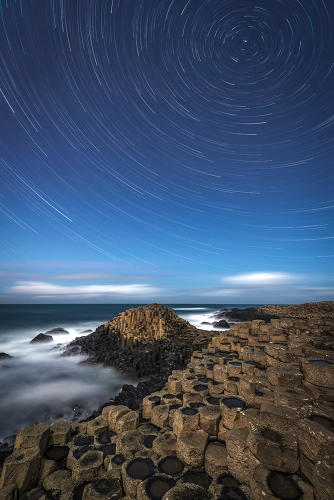 <p>A composition of several images showing how our planet's rotation draws the stars out into circles. Separated from the sky by the stark line of the horizon, the atomic symmetries of crystallized rock turn into hexagonal columns at the Giant's Causeway in Northern Ireland.</p>