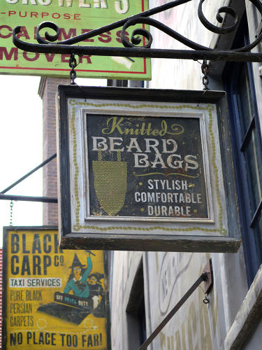 <p>To convey Diagon Alley's age, MinaLima made much of their signage look intentionally weathered, with ghost-lettering, faded paint, and vintage wood.</p>