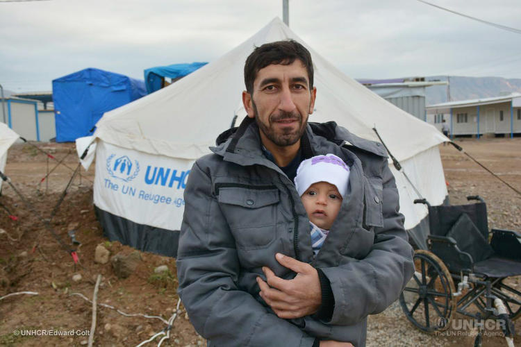 <p>At the Basirma Refugee Camp in northern Iraq, 34-year-old Esam cuddles his infant son Rawan in his winter . The Syrian refugee is living in a tent, made warmer this winter with a UNHCR tent insulation kit and a kerosene heater.</p>