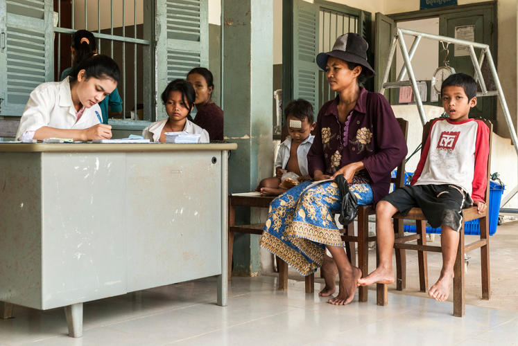 <p>&quot;In the rural province of Siem Reap, a woman waits with two children for a routine prenatal visit under a joint scheme between the local government health centers and an NGO-funded hospital.&quot;</p>