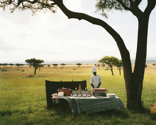 <p>A chef from a nearby luxury lodge waits for his guests to arrive from a hot air balloon excursion before serving them champagne in the middle of the Maasai Mara National Reserve, Kenya. 2012</p>
