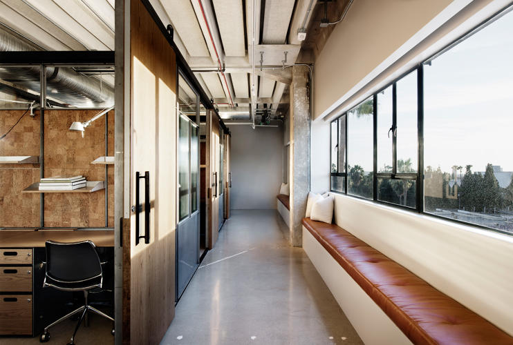 <p>Custom partition systems with mill finished steel and ribbed glass create semi-private workspaces with views to the outside.</p>