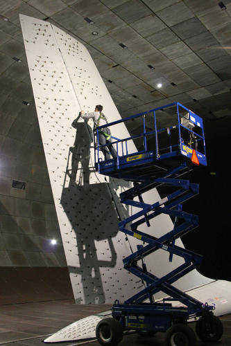 <p>Inside the largest wind tunnel in the world, a researcher preps a test of the system's nozzles. Image: NASA Ames Research Center.</p>
