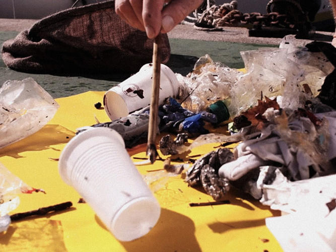 <p>A (partially-recycled) plastic trashcan  sits underwater at the end of a pole. The base of the can is connected to a pipe, which is connected to a pump up at the surface.</p>