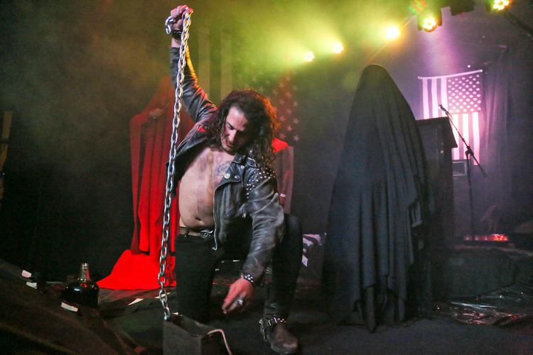 <p>A man pounds his chain-wrapped fists into the ground as Jex Blackmore stands behind him at Austin's The Sidewinder.</p>