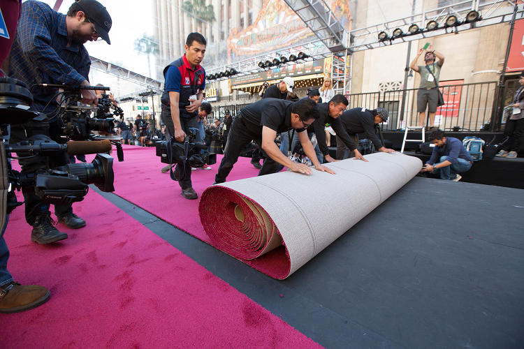 <p>Workers lay out the 500-foot-long and 33-foot-wide red carpet along the Hollywood Boulevard entrance to the Dolby Theatre.</p>
