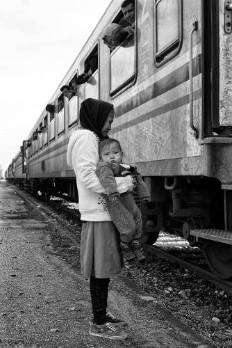 <p>Slovenia, 2015: After arriving by train at Središče ob Dravi, Slovenia, a mother and baby wait for buses provided by the Slovenian authorities to take them further along their journey towards Western Europe. ©Tom Stoddart</p>