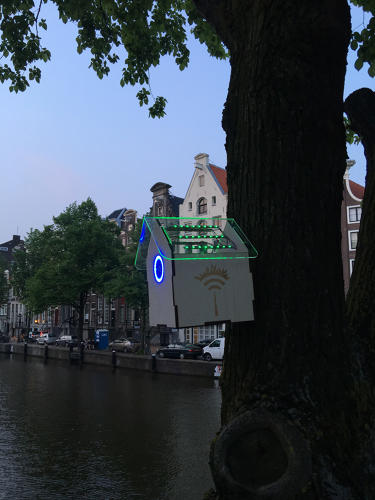 <p>On a tree next to a canal in Amsterdam, a tiny birdhouse glows bright green when the air is clean.</p>