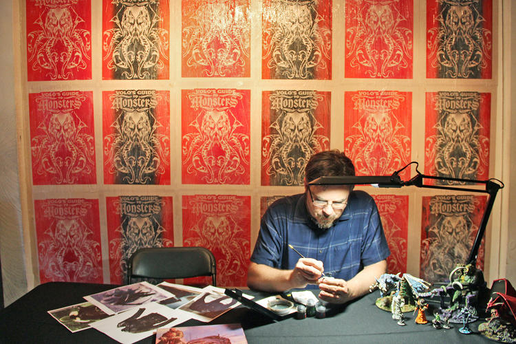 <p>Dreamworks artist Cundo Rabaudi, an event special guest, paints <em>D&amp;D</em> figurines against a wall of limited-edition <em>D&amp;D</em> art.</p>