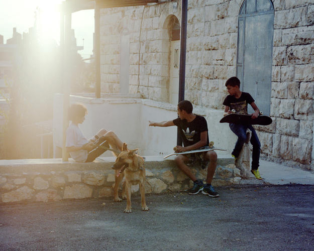 <p>Kids looking after their friend's dog at the Ramallah Youth club.</p>