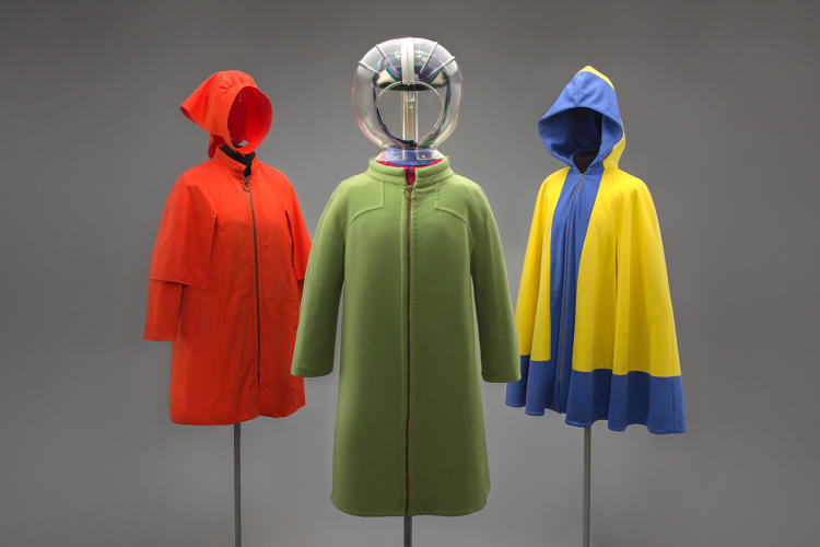 <p>Left to right: Trans World Airlines hostess cape coat and head overing, 1968; Braniff International Airways hostess uniform overcoat, hat scarf, and rain dome by Emilio Pucci, 1965; Hughes Airwest hostess hooded cloak by Mario Armond Zamparelli c. 1972</p>