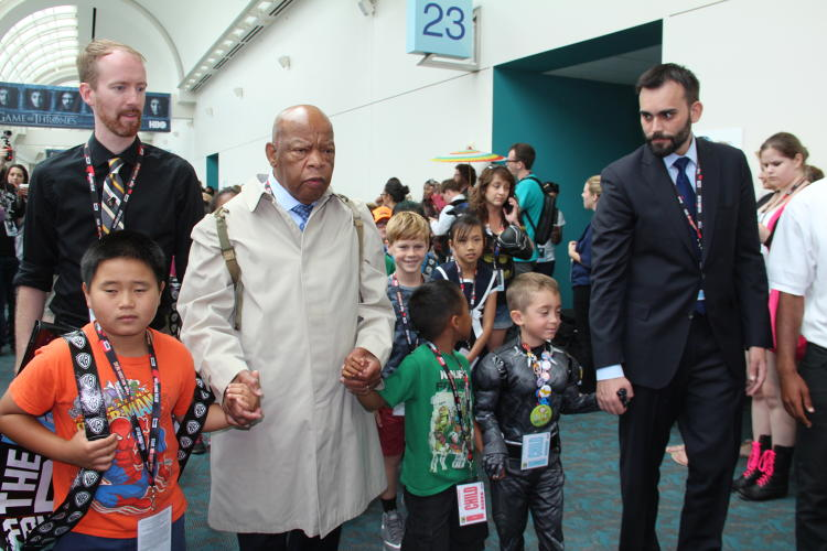 <p>John Lewis, Nate Powell, and Andrew Aydin lead a march at San Diego Comic Con from their panel to the convention floor.</p>