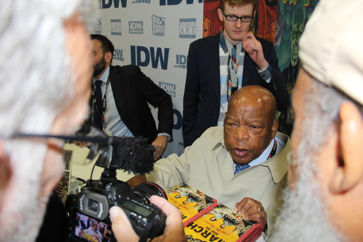 <p>Fans push for a photo of John Lewis as Leigh Walton looks on.</p>
