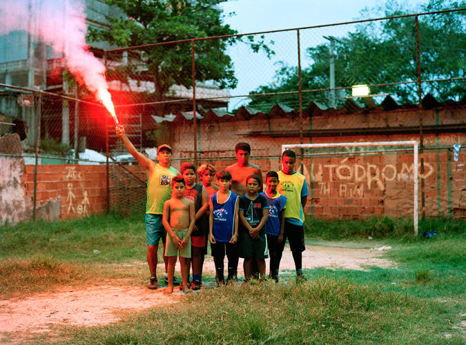 <p>Trainer Luis and the team of young soccer players in Favela Vilà Autodromò before the demolition of the playground in the background.</p>
