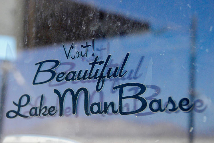 <p>A sticker on the office shed at the Man build site in Black Rock City reads &quot;Visit Beautiful Lake Man Base.&quot;</p>