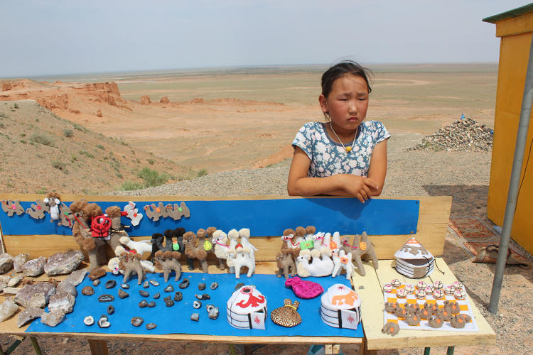 <p>A girl sells souvenirs at the Flaming Cliffs tourist market.</p>
